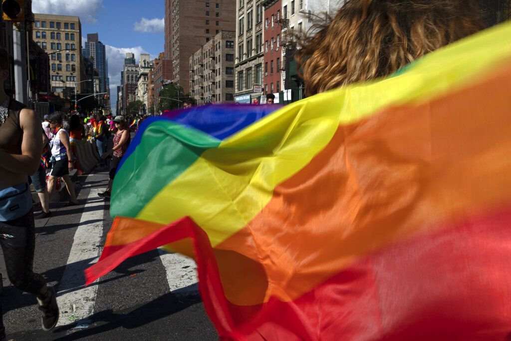 Parade-goers carrying rainbow flags walk down a street in 2019 during the LBGTQ Pride march in New York marking the 50th anniversary of the police raid that sparked the modern-day gay rights movement. (AP Photo/Wong Maye-E, File)
