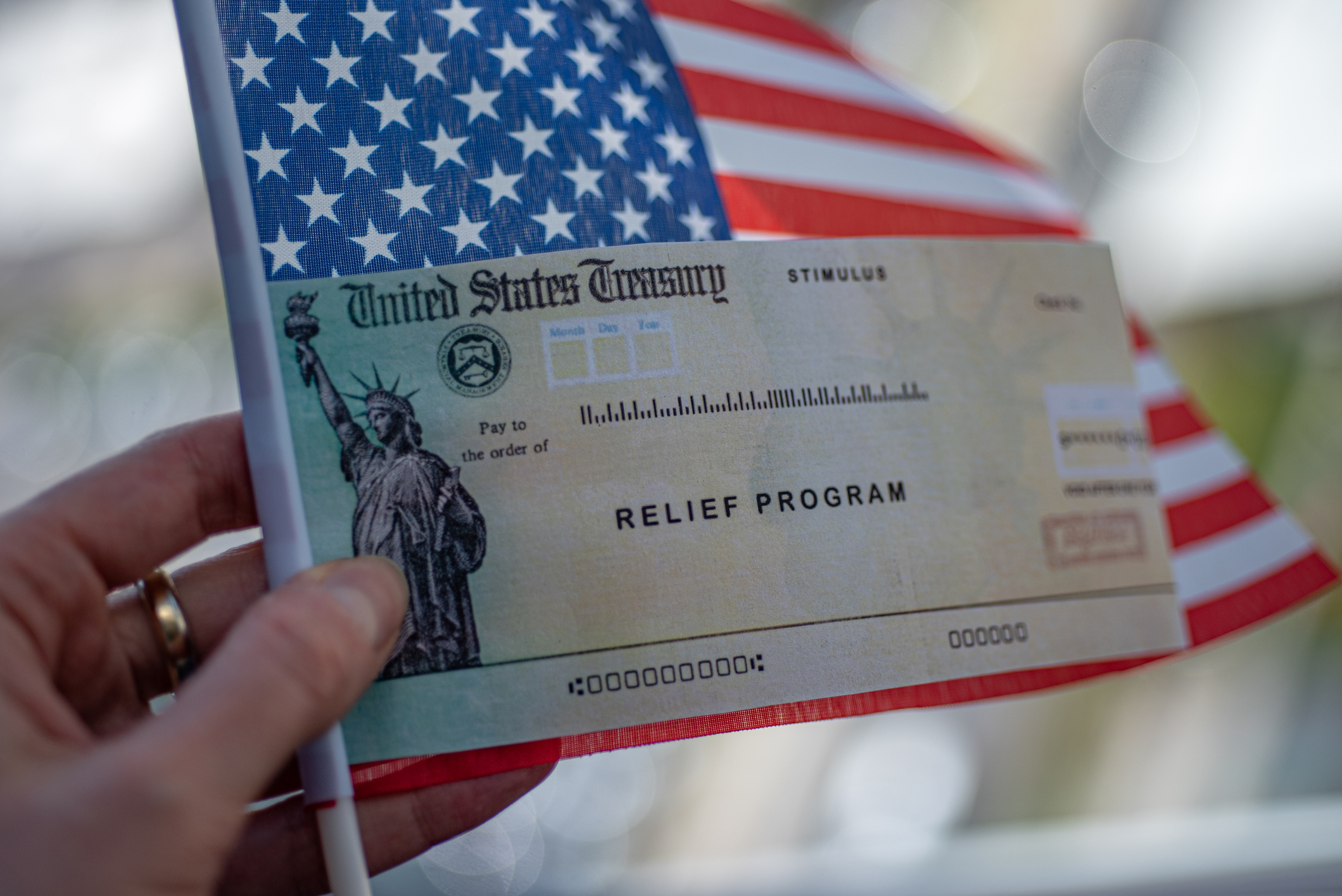 COVID-19 economic Stimulus check on blurred USA flag background. Relief program concept.