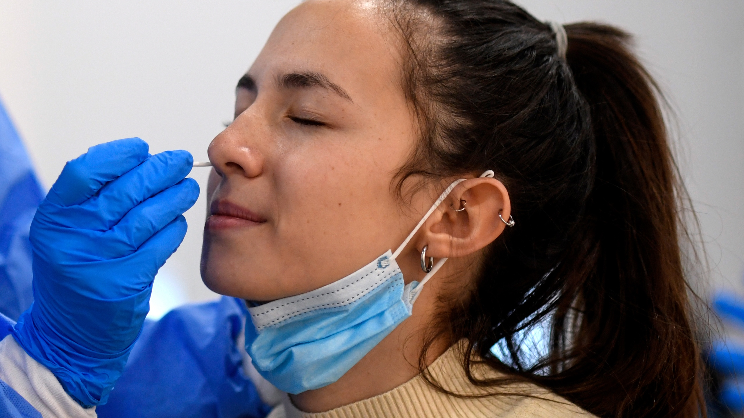 A medical worker takes a swab sample from a woman in Madrid, on Thursday while testing for potential coronavirus cases. (Photo by OSCAR DEL POZO/AFP via Getty Images)