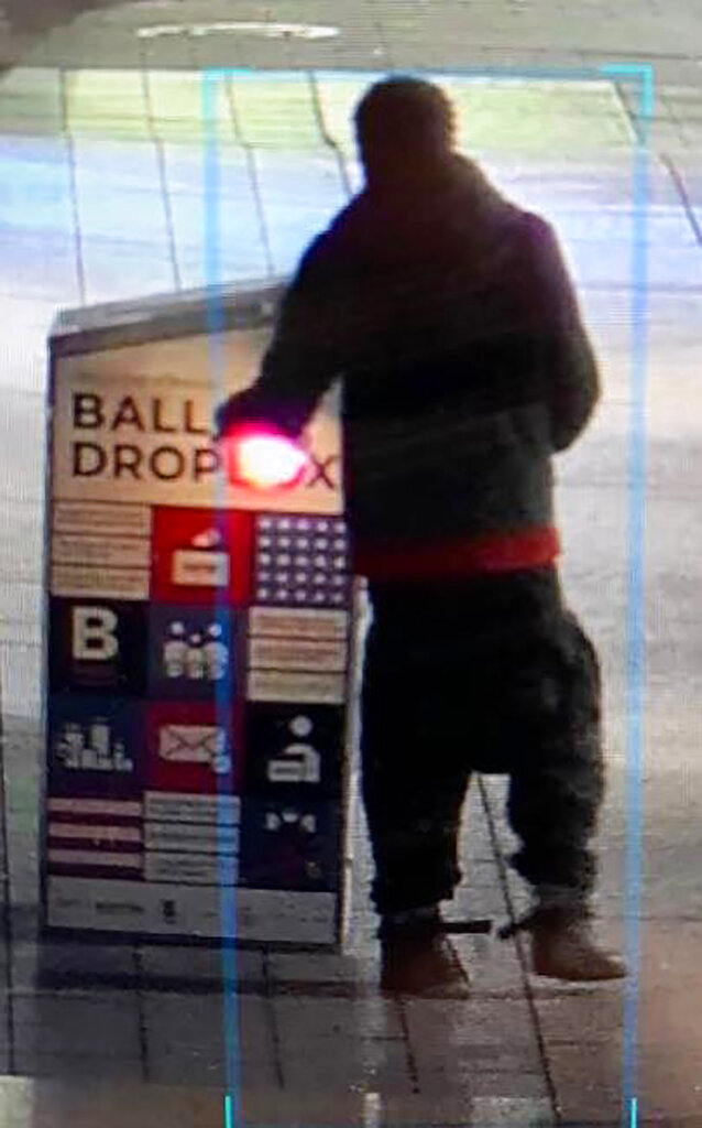 "This surveillance image provided by the Boston Police Department shows a man approaching a ballot drop box outside the Boston Public Library, early Sunday in downtown Boston. Massachusetts election officials say a fire was set at the ballot drop box holding more than 120 ballots in what appears to have been a ""deliberate attack."" Boston Police say that an arson investigation is underway and the person shown in this surveillance image is a person of interest. (Courtesy of Boston Police Department via AP)"