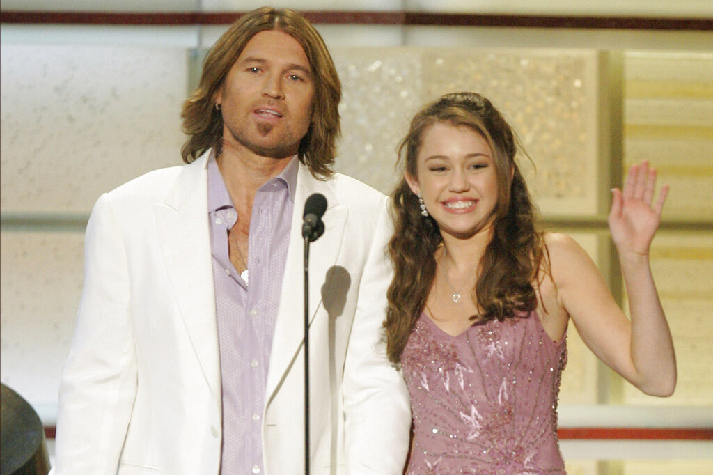 """Billy Ray Cyrus and his daughter, actress Miley Cyrus, present an award during the 41st Academy of Country Music Awards in Las Vegas in 2006. On Friday, The Associated Press reported on stories circulating online incorrectly asserting at a Miley Cyrus concert in 1993, the pop singer told a 9-year-old girl that anything was possible as long as you believed in God. The little girl said she believed in God and was going to become famous one day by stopping Obamacare and making it illegal to kill babies. That little girl grew up to be Judge Amy Coney Barrett, who has been nominated to a Supreme Court seat. Cyrus was born in 1992 and was only 1 year old in 1993. Barrett, a 48-year-old judge, began her legal career in the late 1990s, when Cyrus was still a child. The Affordable Care Act, also known as """"Obamacare,"""" was not enacted until 2010. (AP Photo/Mark J. Terrill)"""