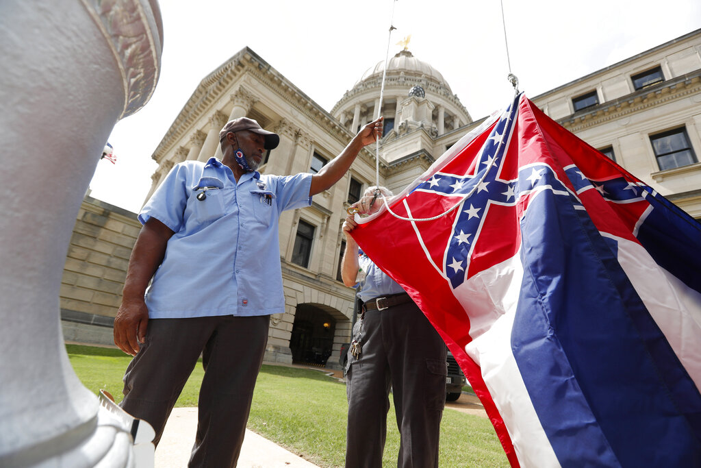 Mississippi Department of Finance and Administration employees Willie Townsend, left, and Joe Brown, attach a Mississippi state flag to the harness before raising it over the Capitol grounds in Jackson, Miss. in June. State legislators voted in June to retire the last state flag in the U.S. bearing the Confederate battle emblem, and voters will decide on Nov. 3, 2020 whether to accept a new flag with a magnolia design. (AP Photo/Rogelio V. Solis)