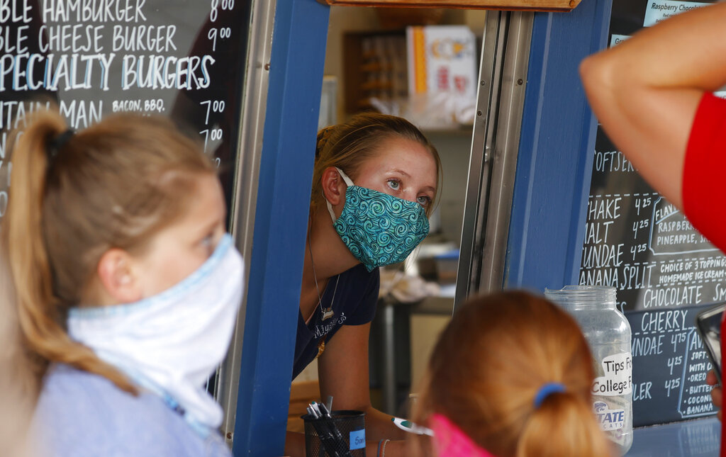 A staffer wears a mask while taking orders at a small restaurant in Grand Lake, Colo., amid the coronavirus pandemic. The pandemic has put millions of Americans out of work, but many of those still working are fearful, distressed and stretched thin, according to a new poll by The Associated Press-NORC Center for Public Affairs Research. (AP Photo/David Zalubowski, File)