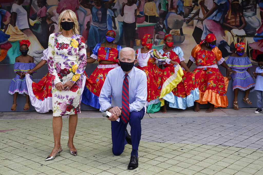Democratic presidential candidate former Vice President Joe Biden and his wife Jill Biden pose for a photo with dancers as they visit Little Haiti Cultural Complex in Miami on Monday. Photos circulating online incorrectly asserted Biden was taking a knee during the national anthem during this campaign event. His campaign confirmed he was kneeling to pose for a picture, and the anthem was not played at the event.. (AP Photo/Andrew Harnik)