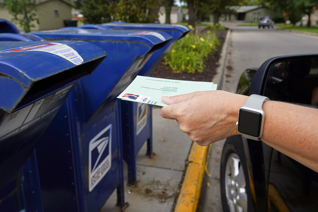 A person drops applications for mail-in-ballots into a mailbox in Omaha, Neb. on August 18, 2020. U.S. Postal Service records show delivery delays have persisted across the country as millions of Americans began voting by mail, raising the possibility of ballots being rejected because they arrive too late. Postal data covering the beginning of October show nearly all of the agency's delivery regions missing agency targets of having more than having more than 95% of first-class mail arrive within five days. (AP Photo/Nati Harnik, File)