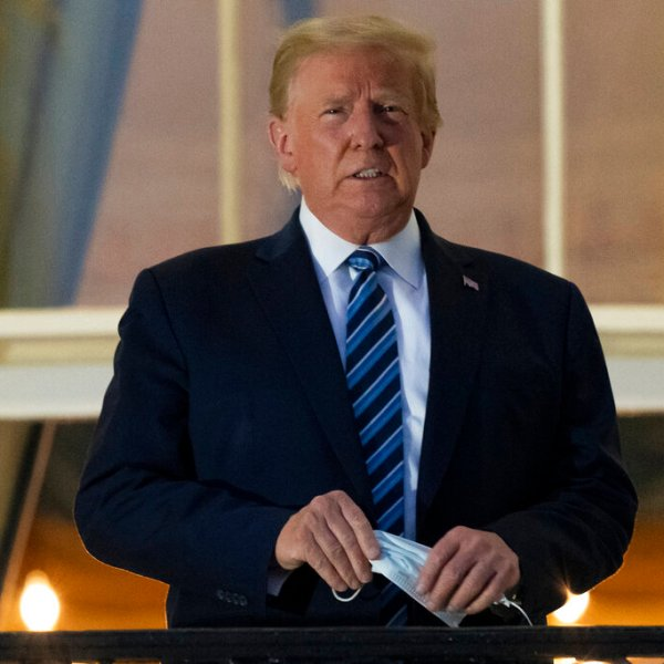 President Donald Trump holds his mask after removing it from his face as he stands on the Blue Room Balcony upon returning to the White House in Washington from the Walter Reed National Military Medical Center. He announced he tested positive for the coronavirus on Oct. 2. (AP Photo/Alex Brandon)