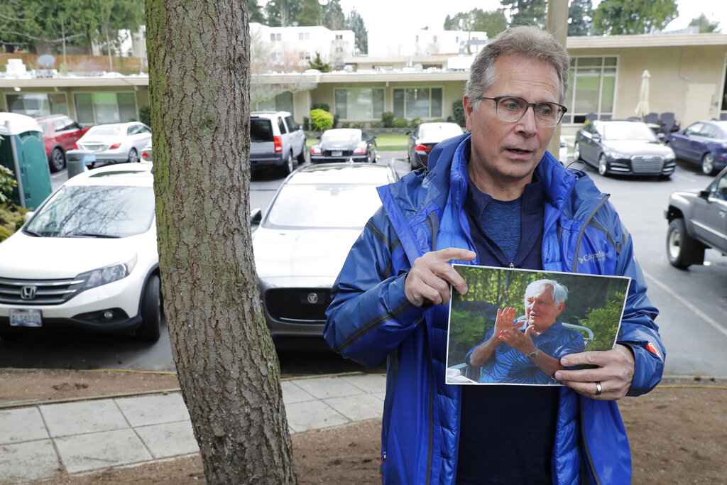Scott Sedlacek poses while holding a photo of his father, Chuck, outside Life Care Center in Kirkland, Wash., in March.. Sedlacek battled COVID-19 while his father also fought the virus and was under care in the facility. Both have since recovered. Hearing of President Donald Trump's advice-by-Tweet on Monday, Oct. 5, 2020, not to fear the disease, as well as Trump's reckless insistence on riding in a motorcade outside Walter Reed Medical Center and on returning to the White House while still infectious, enraged him. (AP Photo/Ted S. Warren, File)