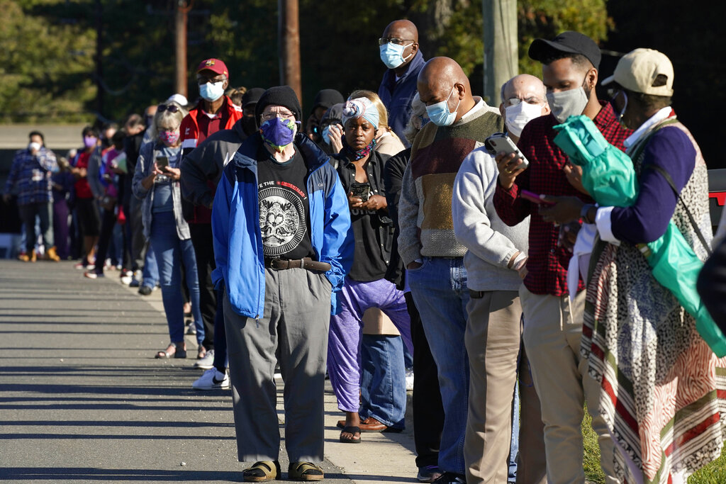 Early voters wait to cast their ballots at the South Regional Library polling location in Durham, N.C., Thursday, Oct. 15, 2020. (AP Photo/Gerry Broome)