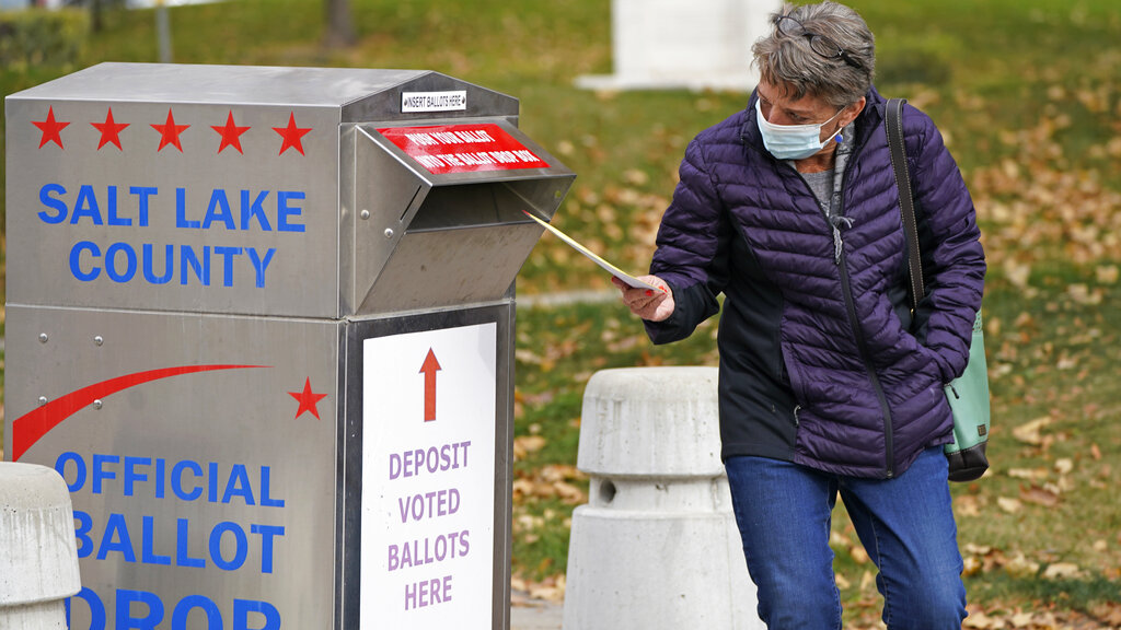 A women inserts her ballot in a ballot drop box Friday in Salt Lake City. (AP Photo/Rick Bowmer)