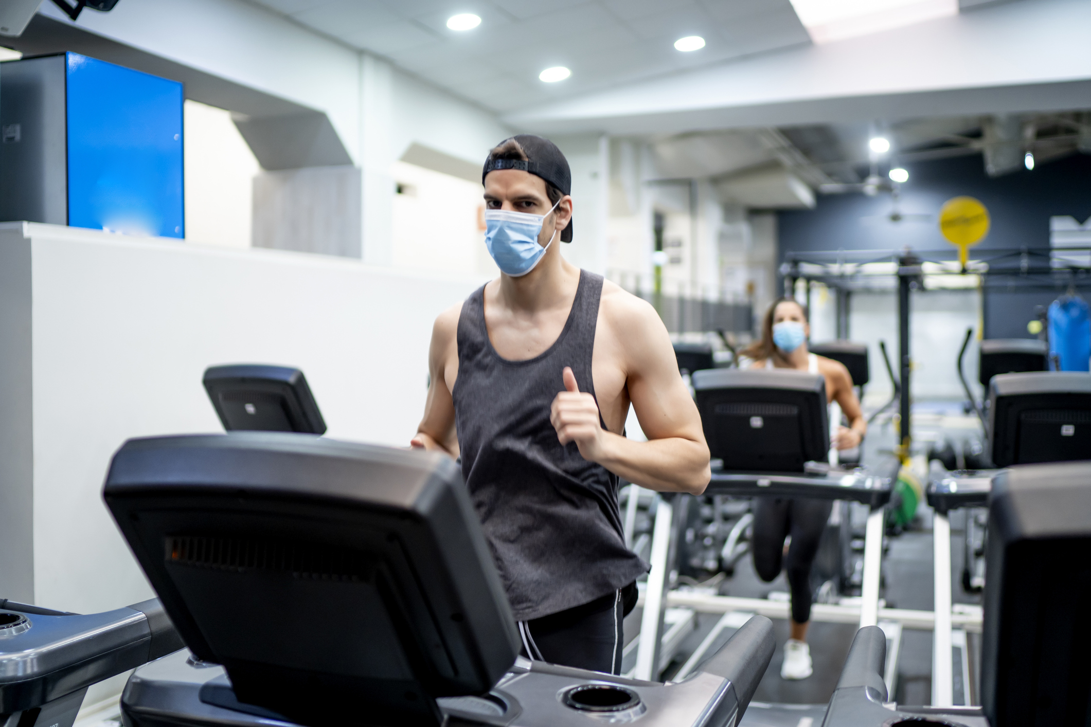 Several young people running on treadmill in gym wearing face mask.