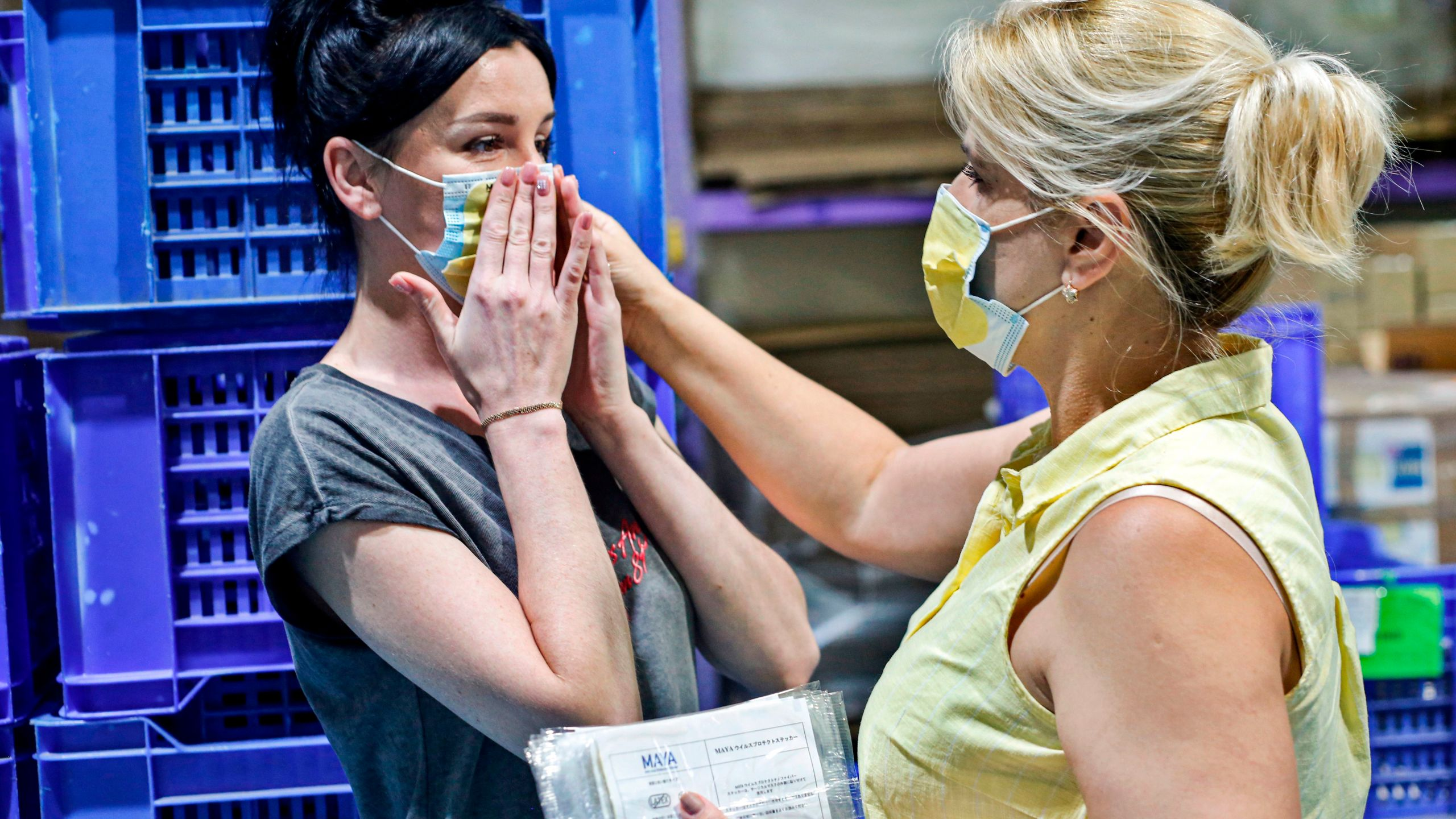 "A worker attaches an anti-viral sticker onto the face mask of a colleague at the Dykam plant which produces them, at Kibbutz Ein Harod near Israel's northern city of Afula. The 3D-printed stickers, called ""Maya"", were developed at the Technion-Israel Institute of Technology to be used as attachments onto face masks for better protection during the COVID-19 coronavirus pandemic. (Photo by GIL COHEN-MAGEN/AFP via Getty Images)"