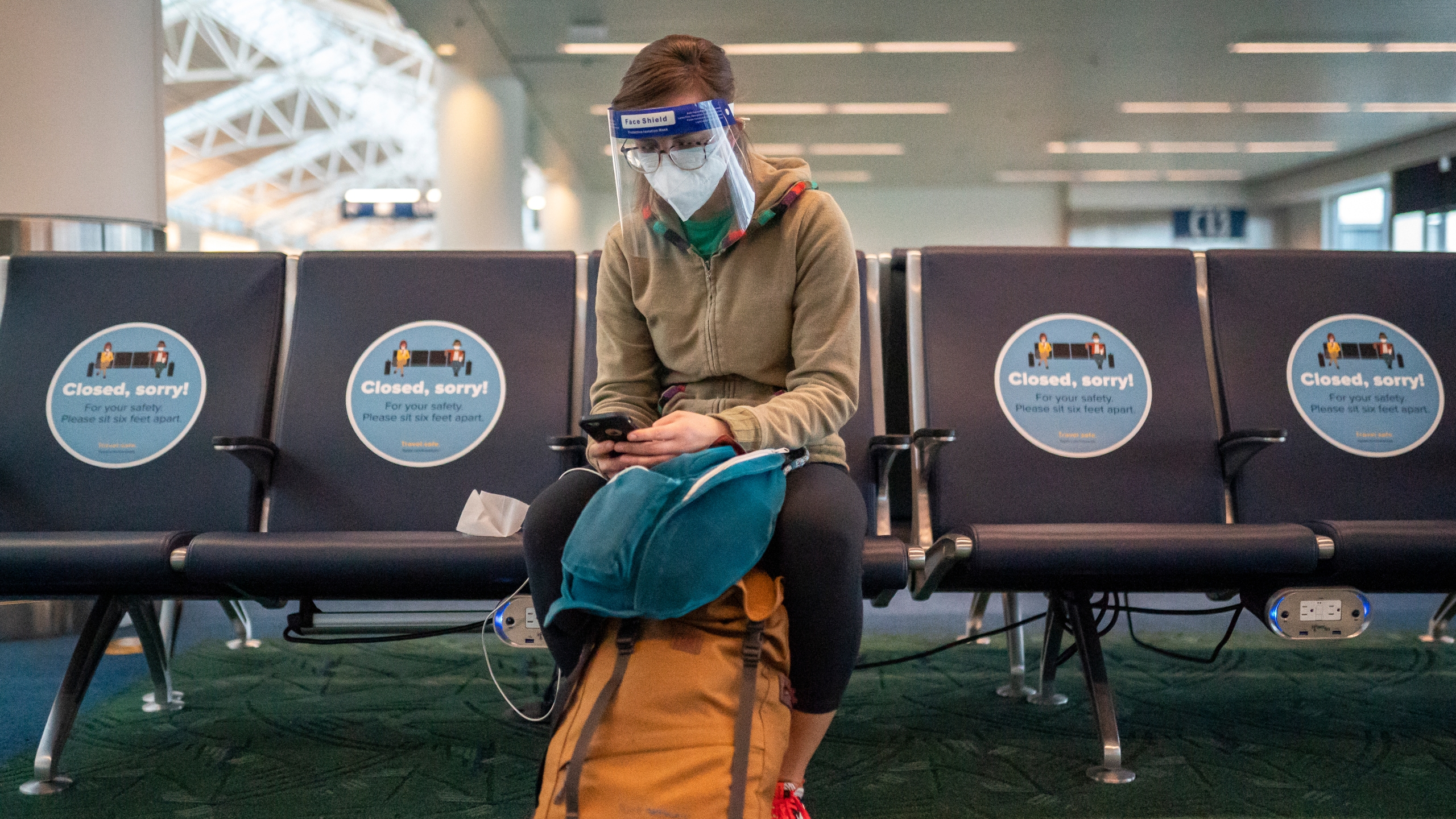 A traveler checks their phone while waiting for a flight at Portland International Airport on November 25, 2020 in Portland, Oregon. Millions of Americans traveled by plane ahead of the Thanksgiving holiday, despite the CDC recommending families stay home. (Photo by Nathan Howard/Getty Images)