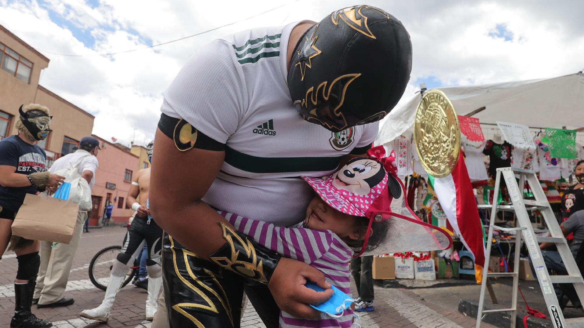 A girl hugs Mexican Lucha Libre wrestler Ciclonico