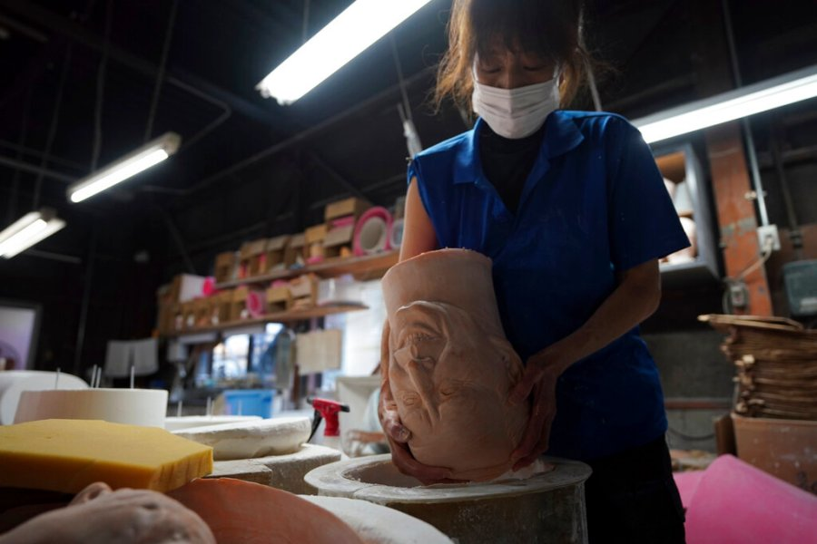 An employee prepares a mold for the rubber masks. (AP Photo/Eugene Hoshiko)