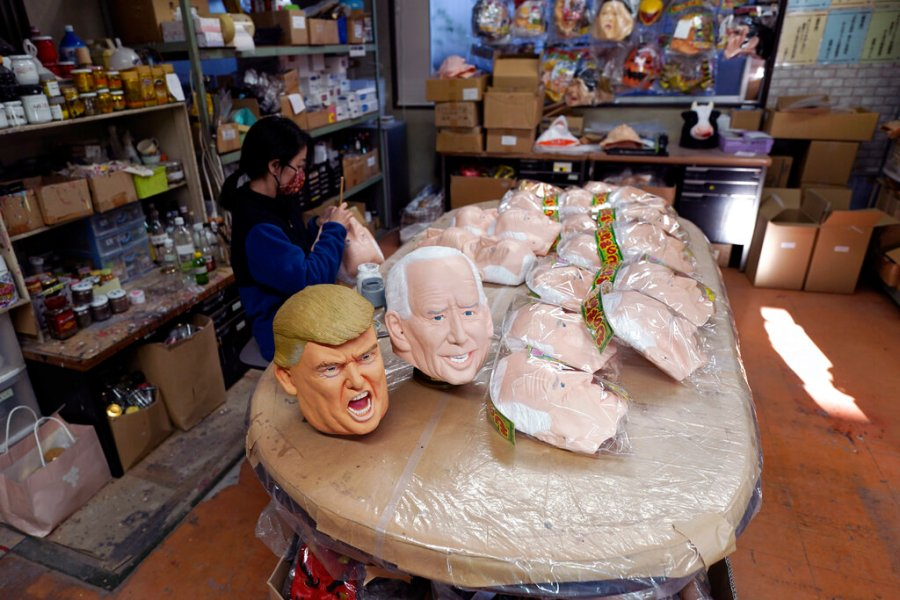 An employee adds details to rubber masks depicting President-elect Joe Biden. (AP Photo/Eugene Hoshiko)