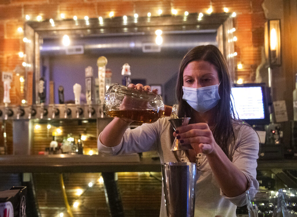 Bartender Kellie Mottiqua prepares drinks at Bridgetown Taphouse in Ambridge, Penn. Earlier in the day Gov. Tom Wolf and Health Secretary Rachel Levine announced a series of orders and advisories, including a stay-at-home advisory, and an order suspending all alcohol sales in bars, restaurants or catered events during the night before Thanksgiving. (Emily Matthews/Pittsburgh Post-Gazette via AP)