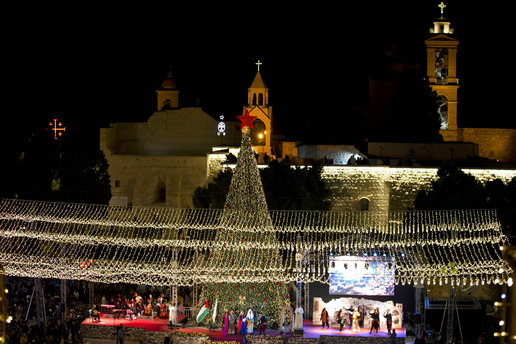 Palestinian Christians celebrate the lighting of a Christmas tree outside the Church of the Nativity, traditionally believed by Christians to be the birthplace of Jesus Christ in the West Bank city of Bethlehem, in 2019. The Palestinian Health Ministry has recommended strict limits on Christmas celebrations in Bethlehem this year due to the coronavirus outbreak. Celebrations in the biblical town revered by Christians as Jesus' birthplace are usually attended by thousands of people from around the world. (AP Photo/Majdi Mohammed)