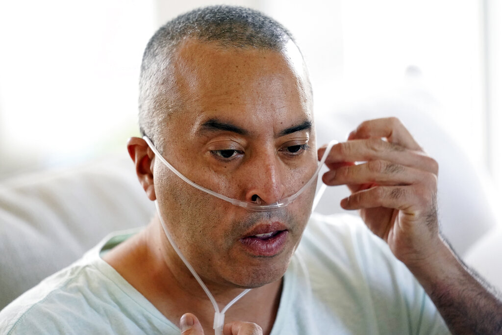 Antonio Gomez breathes with the help of an oxygen tank at home in Simi Valley, Calif. Gomez is recovering at home after a three-week bout with COVID-19, which included a 12-day stay in the hospital. (AP Photo/Marcio Jose Sanchez)