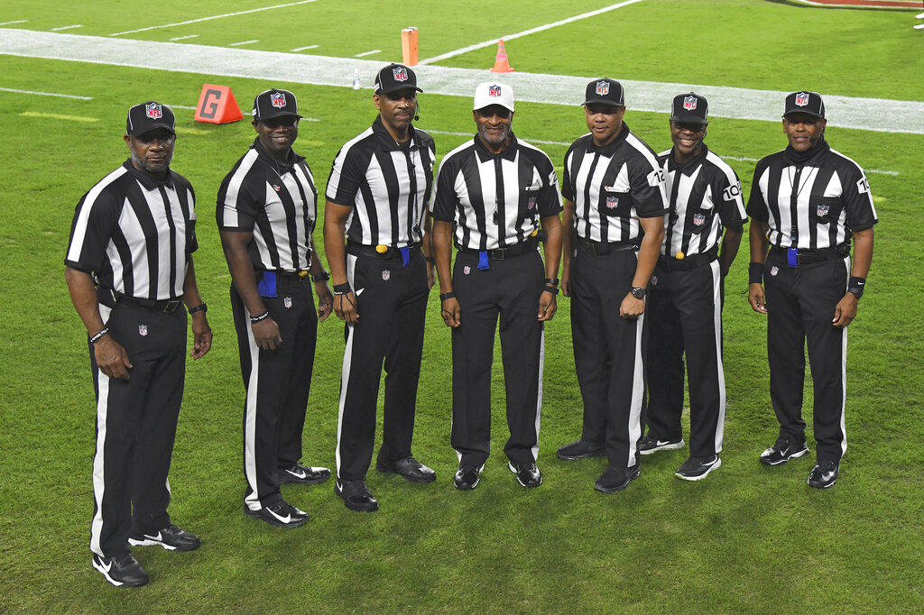 NFL officials, from left, umpire Barry Anderson, side judge Anthony Jeffries, down judge Julian Mapp, referee Jerome Boger, back judge Greg Steed, field judge Dale Shaw (104), line judge Carl Johnson (101) pose for a photo before an NFL football game between the Tampa Bay Buccaneers and the Los Angeles Rams, in Tampa, Fla. The game is the first in NFL history to feature an all African-American officiating crew. (AP Photo/Jason Behnken)