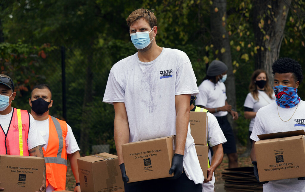 Former Dallas Mavericks star Dirk Nowitzki wears a mask to prevent the spread of COVID-19 as he helps other volunteers distribute food aid to the public during a North Texas Food Bank drive-thru event in Dallas in October. (AP Photo/LM Otero)