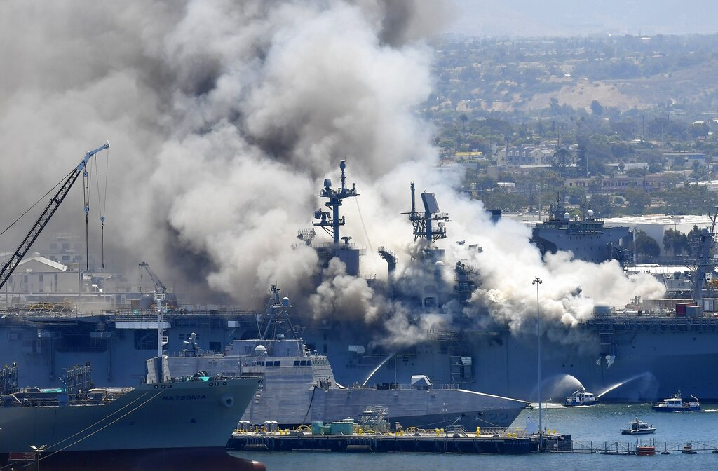 Smoke rises from the USS Bonhomme Richard at Naval Base San Diego in San Diego, after an explosion and fire onboard the ship In this July 12, 2020, file photo. The Navy said on Monday that it will decommission the warship after suspected arson caused extensive damage, making it too expensive to restore. (AP Photo/Denis Poroy, File)