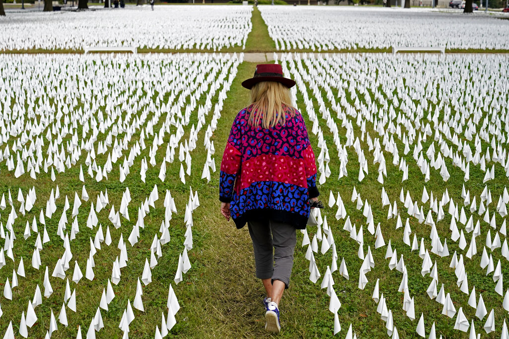 Artist Suzanne Brennan Firstenberg walks among thousands of white flags planted in remembrance of Americans who have died of COVID-19 near Robert F. Kennedy Memorial Stadium in Washington. Regardless of the presidential election outcome, a vexing issue remains to be decided: Will the U.S. be able to tame a perilous pandemic that is surging as holidays, winter and other challenges approach? Public health experts fear the answer is no, at least in the short term, with potentially dire consequences. (AP Photo/Patrick Semansky, File)