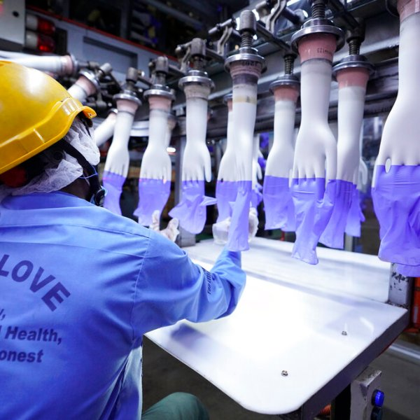 A worker inspects disposable gloves at the Top Glove factory in Shah Alam on the outskirts of Kuala Lumpur, Malaysia. Malaysia's Top Glove Corp., the world's largest rubber glove maker, said Tuesday it expects a delay in deliveries after it was hit by a coronavirus outbreak that affected thousands of workers. (AP Photo/Vincent Thian