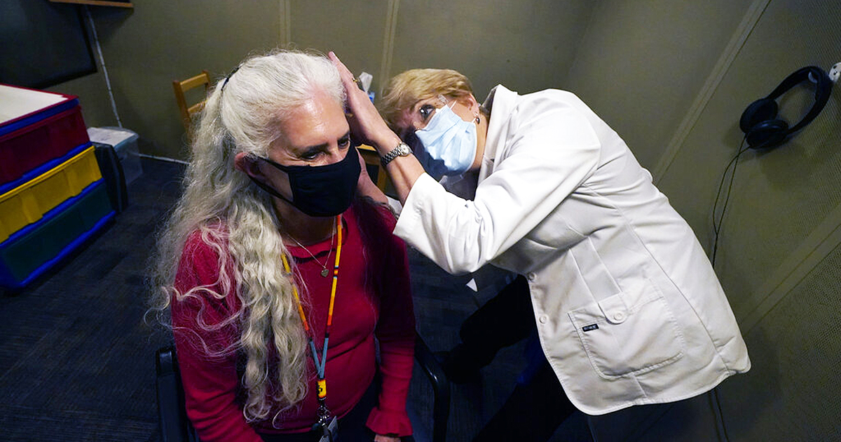 Andrea Gohmert, right, director of the hearing clinic at the University of Texas at Dallas' Callier Center for Communication Disorders, prepares Lynne Perler for a hearing test. Hearing specialists across the U.S. are seeing an uptick in visits from people who only realized how much they relied on lip reading and facial expressions when people started wearing masks because of the coronavirus pandemic. (AP Photo/LM Otero)
