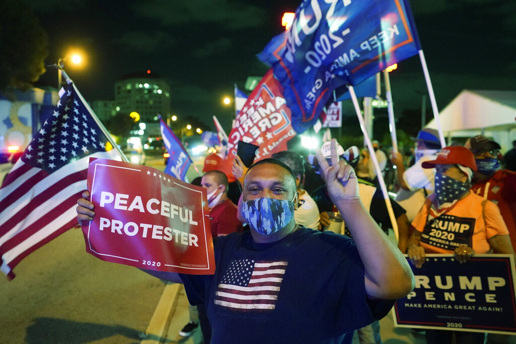 Supporters of President Donald Trump chant and wave flags outside the Versailles Cuban restaurant in the Little Havana neighborhood of Miami during an Election Night celebration. Trump and his Republican allies made significant inroads with Latino voters in Tuesday's election, alarming some Democrats who warned that immigration politics alone was not enough to hold their edge with the nation's largest minority group. (AP Photo/Wilfredo Lee)