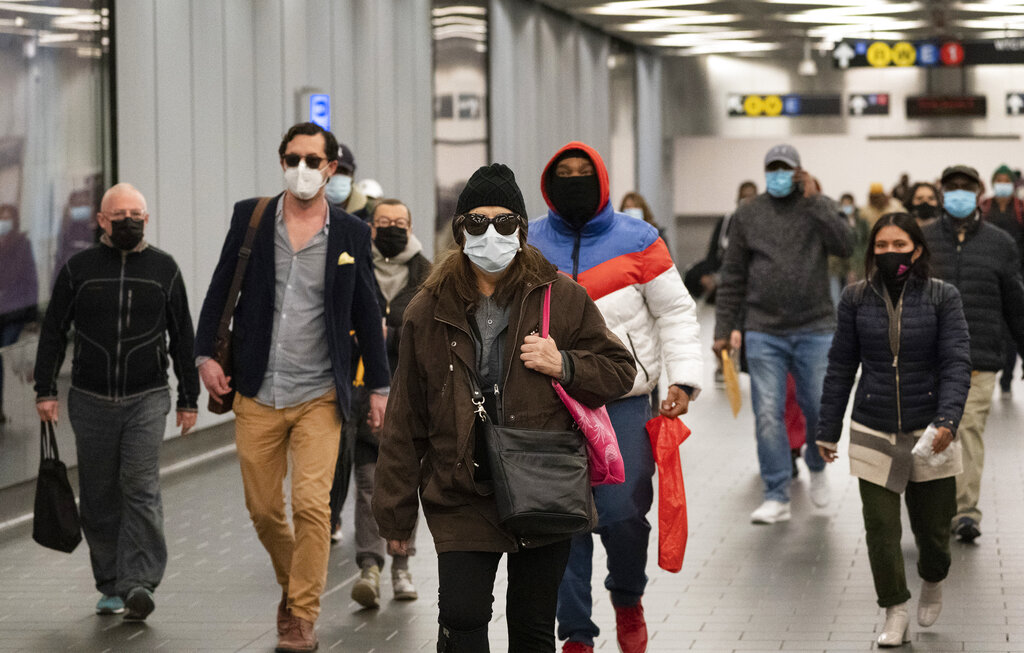 Commuters wear face masks while walking through the World Trade Center's transportation hub in New York. Despite the expected arrival of COVID-19 vaccines before the end of 2020, it could be well into 2021 before things get back to something close to normal. (AP Photo/Mark Lennihan, File)
