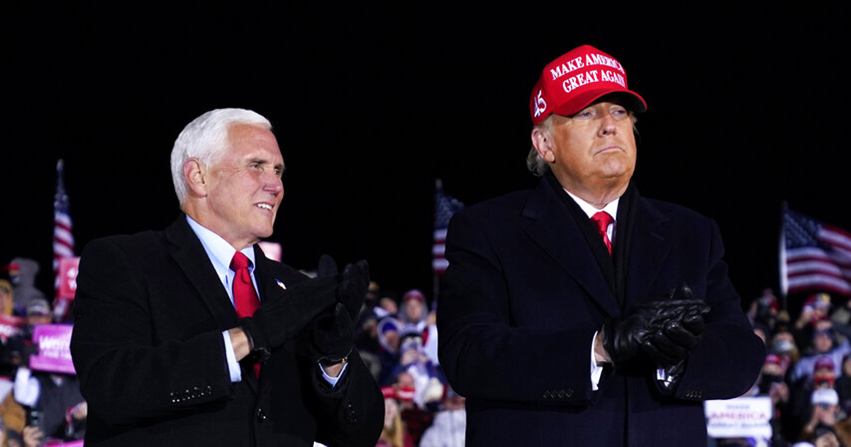 President Donald Trump and Vice President Mike Pence stand on stage after a campaign rally at Gerald R. Ford International Airport, early Tuesday, Nov. 3, in Grand Rapids, Mich. (AP Photo/Evan Vucci)