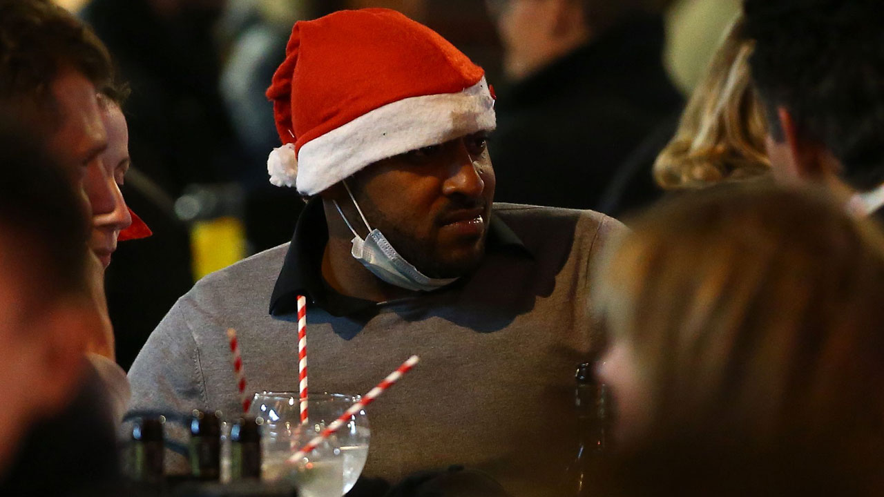 A man sits at a table with others outside a bar in central London on the eve of a second COVID-19 lockdown in an effort to combat soaring infections. English pubs called last orders at the bar for a month on Wednesday evening, as the country effectively shuts down from November 5, for the second time this year to try to cut coronavirus cases. (Photo by HOLLIE ADAMS/AFP via Getty Images)