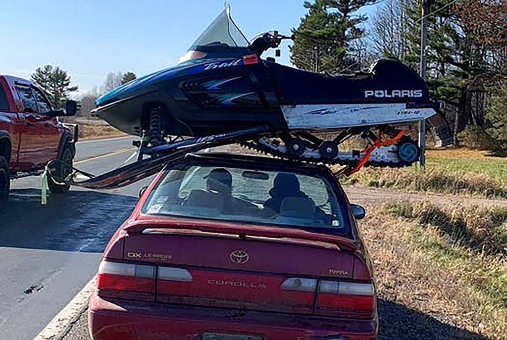 This undated photo provided by The Wisconsin Department of Transportation shows a snowmobile strapped to the roof of a Toyota Corolla in Northwestern Wisconsin on Sunday. The Wisconsin State Patrol pulled over the driver after seeing the snowmobile perched sideways on top of the sedan. The Wisconsin Department of Transportation says the 23-year-old driver from Clayton explained to the trooper that he had just purchased the snowmobile was headed to a friend's house to show it to him. (Wisconsin Department of Transportation via AP)