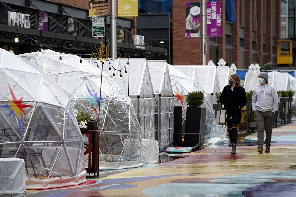 People walk by outdoor plastic dining bubbles on Fulton Market in Chicago. (AP Photo/Nam Y. Huh File)