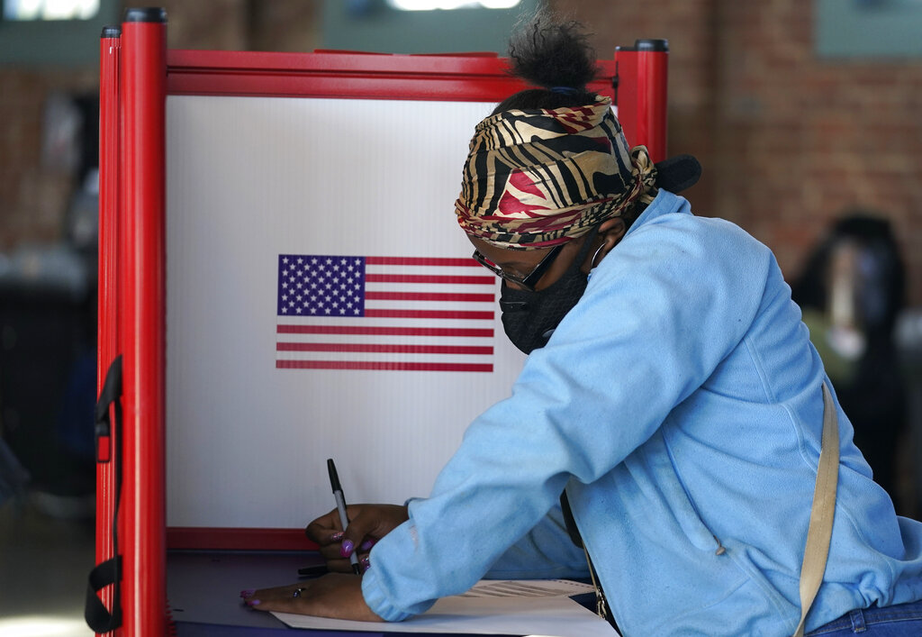 Johnea Barlow casts her ballot at the Kentucky Center for African American Heritage, on Election Day in Louisville, Ky. The 2020 presidential election had all the makings of a looming disaster: fears of Russian meddling, violence at the polls, voter intimidation and poll workers fleeing their posts over the coronavirus. But the election was largely smooth, in large part because 107 million voters that cast their ballots early and took the pressure off Election Day operations. (AP Photo/Darron Cummings, File)