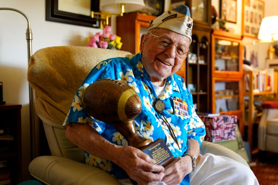 Mickey Ganitch, a 101-year-old survivor of the attack on Pearl Harbor, holds a football statue he was given in the living room of his home in San Leandro, Calif., Nov. 20, 2020. Ganitch was getting ready for a match pitting his ship, the USS Pennsylvania, against the USS Arizona when Japanese planes bombed Pearl Harbor on Dec. 7, 1941. The game never happened. (AP Photo/Eric Risberg)