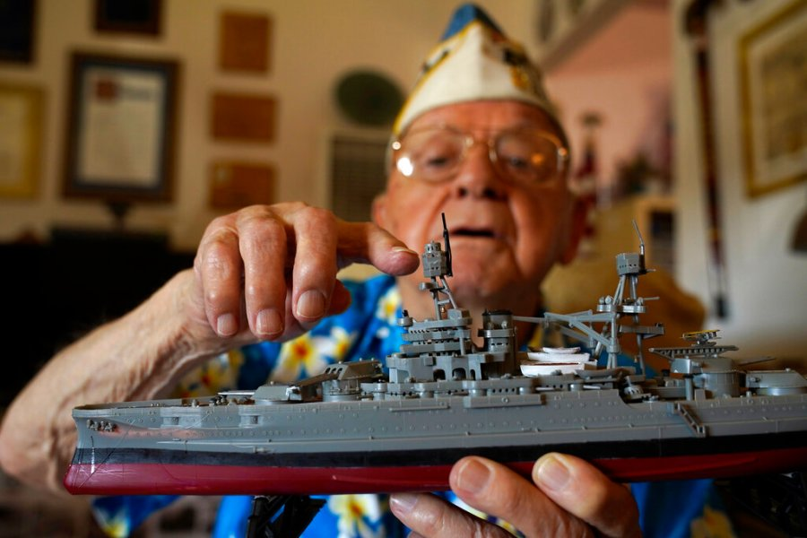Mickey Ganitch holds up a model of the USS Pennsylvania and points to where he served as a lookout during the 1941 attack on Pearl Harbor. The 101-year-old has traveled to Hawaii for the anniversary of the attack almost every year of the past 15 to remember those killed. But this year, nearly eight decades after the bombing that launched the U.S. into World War II, the coronavirus pandemic is forcing him to observe the moment from afar in California. (AP Photo/Eric Risberg)
