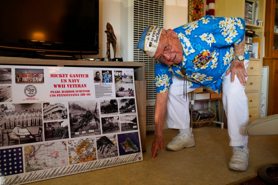 101-year-old Mickey Ganitch, a survivor of the attack on Pearl Harbor, drops down to display his football stance in the living room of his home in San Leandro, Calif. (AP Photo/Eric Risberg)