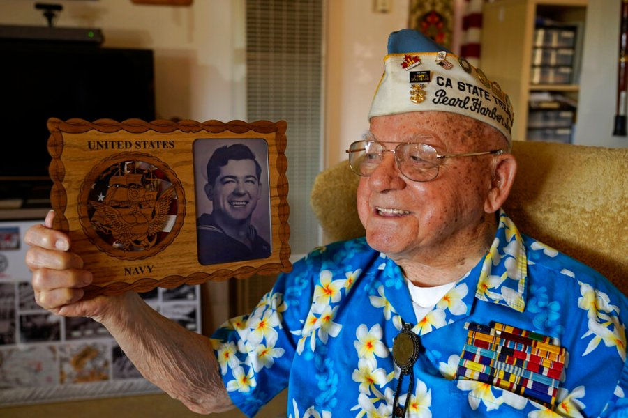 Mickey Ganitch, a survivor of the 1941 attack on Pearl Harbor, holds a plaque with a picture of himself as a young sailor. (AP Photo/Eric Risberg)