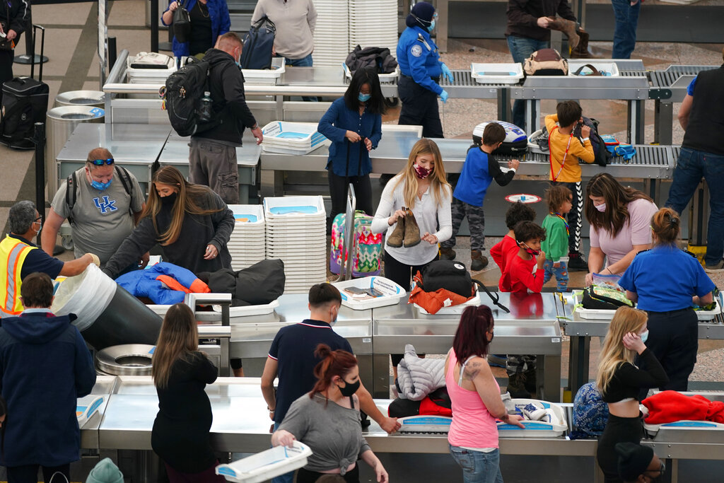 Travelers wear face masks while passing through the south security checkpoint in the main terminal of Denver International Airport Tuesday, Dec. 22, 2020, in Denver. (AP Photo/David Zalubowski)