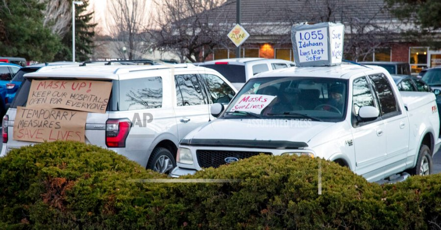 Supporters of health workers and mask mandates held a silent counter protest by decorating their vehicles at an anti-mask protest at the Central District Health offices, Tuesday, Dec. 8, 2020 in Boise, Idaho. (Darin Oswald/Idaho Statesman via AP)