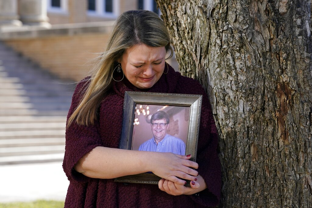 Katie Riggs Maxwell begins to cry as she hugs a portrait of her father Mark Riggs on the campus of Abilene Christian University in Abilene, Texas. Mark Riggs, who was a professor at the school, passed away last Monday of COVID-19. (AP Photo/Tony Gutierrez)