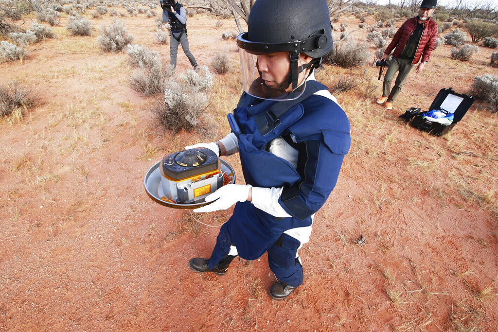 In this photo provided by the Japan Aerospace Exploration Agency (JAXA), a member of JAXA retrieves a capsule dropped by Hayabusa2 in Woomera, southern Australia. The Japanese capsule brought back pieces of Asteroid Ryugu. (JAXA via AP, File)