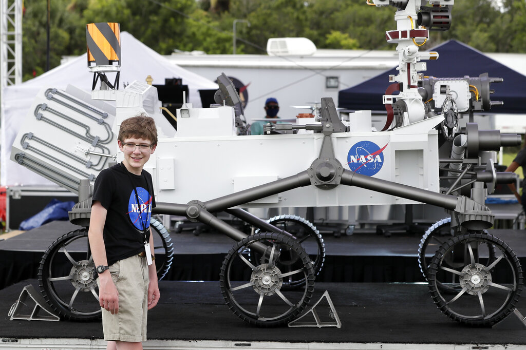 "Alexander Mather, of Burke, Va., stands next to a model of the Mars 2020 rover he named  ""Perseverance"" in a contest, at the Kennedy Space Center in Cape Canaveral, Fla. Launched in July, NASA's Perseverance rover is set to land on Mars on Feb. 18 at an ancient river delta and lakebed where microscopic life may have once flourished. The rover will drill into the dry crust, collecting samples for eventual return to Earth. (AP Photo/John Raoux, File)"