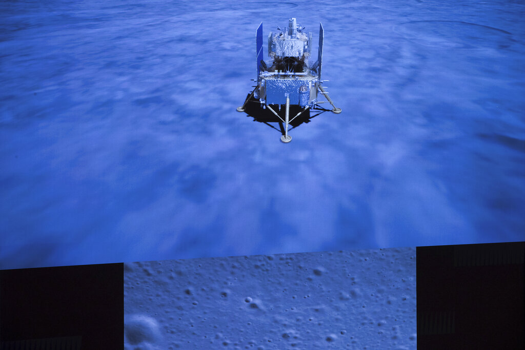 In this photo released by Xinhua News Agency, a display screen in Beijing shows the landed Chang'e-5 spacecraft and a moon surface picture, below, taken by camera aboard Chang'e-5 spacecraft during its landing process. The Chinese spacecraft landed on the moon to bring back lunar rocks to Earth for the first time since the 1970s, the Chinese government announced. (Jin Liwang/Xinhua via AP, File)