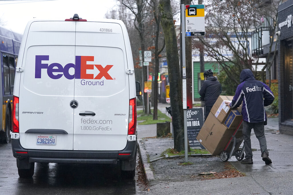 A FedEx driver carries a package away from a van, Tuesday, Dec. 8, 2020, in Seattle. Store are warning online shoppers that if holiday purchases aren't made soon, they may not be delivered in time for Christmas. (AP Photo/Ted S. Warren)