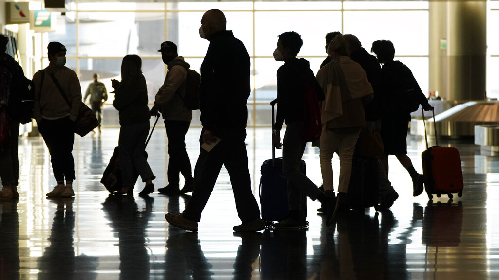 Air travelers line up to go through a a security checkpoint at Salt Lake City International Airport in Salt Lake City. Data from roadways and airports shows millions could not resist the urge to gather on Thanksgiving, even during a pandemic. (AP Photo/Rick Bowmer, File)