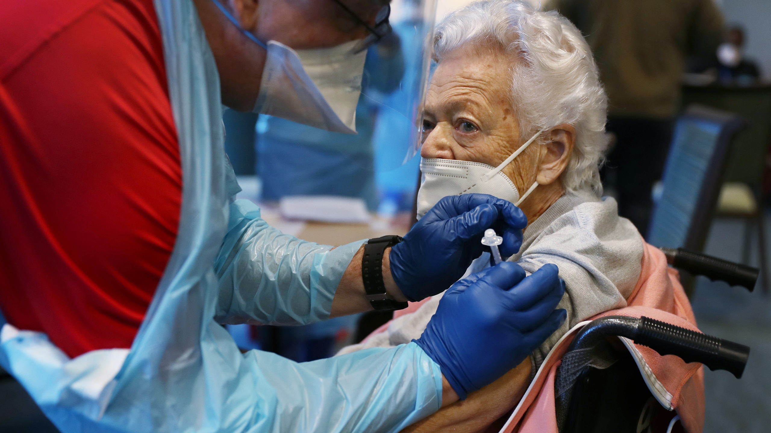 A healthcare worker working with the Florida Department of Health in Broward administers a Pfizer-BioNtech COVID-19 vaccine to Nancy Mathews, 90, at the John Knox Village Continuing Care Retirement Community on January 6 in Pompano Beach, Florida. (Photo by Joe Raedle/Getty Images)