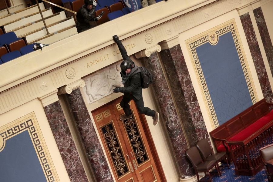 A man identified as Josiah Colt hangs from the balcony in the Senate Chamber on January 06, 2021 in Washington, DC. (Photo by Win McNamee/Getty Images)