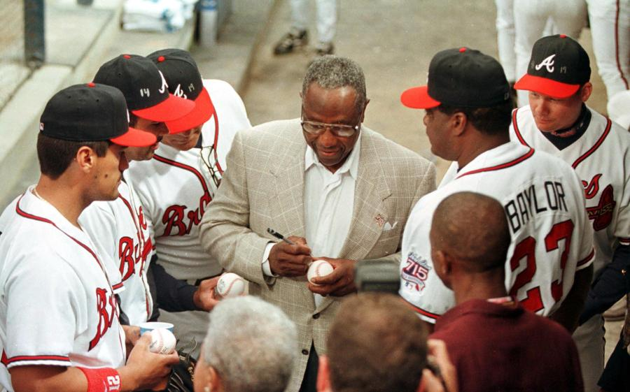 Hank Aaron signs autographs for some of the Atlanta Braves players before ceremonies that unveiled the Hank Aaron Award on the 25th anniversary of his historic 755th home run in1999. The Hank Aaron Award will be based on the player's combined numbers of hits, home runs and RBI and is scheduled to be presented to the best hitter in each league Championship Series. (STEVE SCHAEFER/AFP via Getty Images)